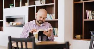 人读坐在旅馆与杯子的大厅咖啡馆的一本书热奶咖啡 股票录像