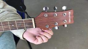 人调整在马丁内斯吉他的调整的钉在灰色背景 股票录像