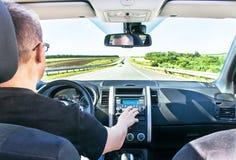 人调整在汽车立体音响(收音机)的音量 免版税库存照片