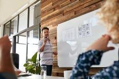 年轻人谈论新的流动应用在创造性的PR期间 免版税库存图片