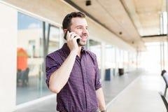 人谈话与使用智能手机的朋友在商城 免版税库存图片