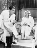 年轻人谈话与坐与他的脚的一名老人浸泡在洗衣盆(所有人被描述不是更长生存和没有ES 免版税库存照片
