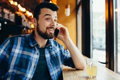 年轻人谈话在咖啡馆的电话 图库摄影