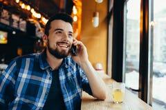 年轻人谈话在咖啡馆的电话 免版税库存照片