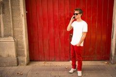 年轻人谈话在电话在城市 免版税库存图片