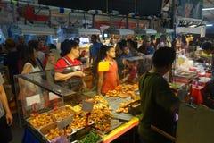 人购买食物在夜市场上 图库摄影