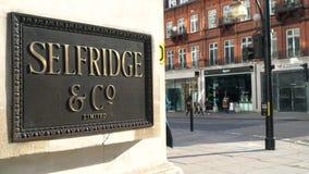 人购物的走通过Selfridges标志,牛津街道,伦敦,英国 股票录像