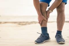 人赛跑者举行他的体育在海滩背景的腿受伤 库存图片