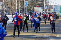 人赛跑者大人群沿积雪的街道跑在鄂木斯克 库存图片