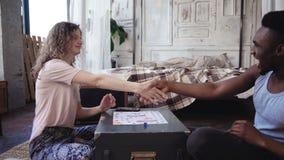 人赢取棋和舞蹈 多种族夫妇亲吻和互相震动手 妇女对胜利祝贺 库存照片