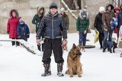 人走与一只德国牧羊犬在冬天 免版税库存图片