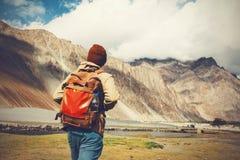 年轻人走往高地山的旅行背包徒步旅行者 免版税库存照片