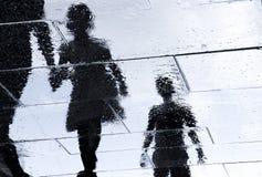 人走的湿城市街道模糊的反射剪影  图库摄影