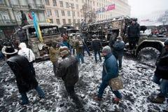 人走的里面城市的被烧的部分有broked汽车和公共汽车的在冬天反政府抗议Euromaidan期间的雪 图库摄影
