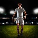 年轻人足球运动员在与球的草地在手中走 库存照片