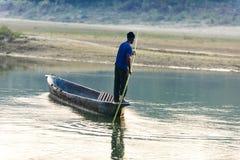 人跑在河,尼泊尔, Chitwan国家公园的一条木小船, 免版税库存照片