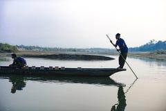 人跑在河,尼泊尔, Chitwan国家公园的一条木小船, 免版税图库摄影