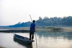 人跑在河,尼泊尔, Chitwan国家公园, 12月的一条木小船 库存图片
