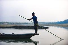 人跑在河,尼泊尔, Chitwan国家公园, 12月的一条木小船 免版税图库摄影