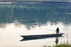人跑在河,尼泊尔, Chitwan国家公园, 12月的一条木小船 图库摄影