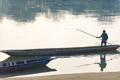 人跑在河,尼泊尔, Chitwan国家公园, 12月的一条木小船 免版税库存图片
