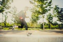 年轻人跑的实践的体育的行动迷离图象在有极端背后照明透镜火光的城市公园 库存照片