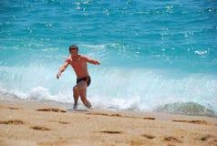 人跑远离波浪 免版税图库摄影