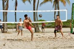 年轻人踢在沙滩排球法院的一个足球 图库摄影