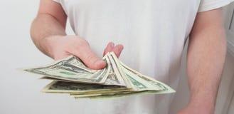人身分佩带的白色T恤杉举行以他的手美国美元 免版税库存图片