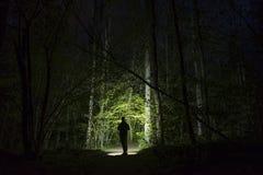人身分室外在发光与手电的黑暗的晚上 免版税库存图片