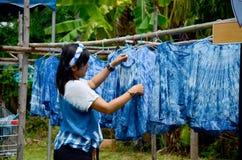 人运作的蜡染布洗染Mauhom颜色过程干燥衣裳 免版税库存图片