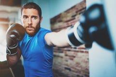年轻人运动员在健身健身房的拳击锻炼在被弄脏的背景 艰苦训练运动的人 脚踢拳击概念 免版税库存图片