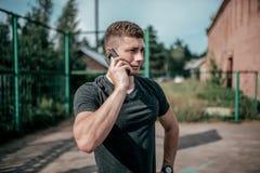 人运动员在电话叫,在锻炼以后,休息在健身锻炼凹凸部以后 夏天在的城市 免版税库存图片