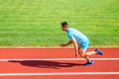 人运动员赛跑者推挤开始状态体育场道路好日子 赛跑者在体育场的短跑种族 被夺取的赛跑者  免版税库存照片
