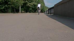 人运动员,在他的自行车和驱动得到远离照相机在没有焦点 股票视频