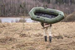 人运载在湖的岸的橡胶可膨胀的小船 免版税库存照片