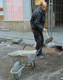 人运载有水泥的独轮车 图库摄影
