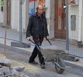 人运载有水泥的独轮车 免版税库存照片