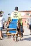 人运载沿海滩木板走道的轻便折叠躺椅 库存图片