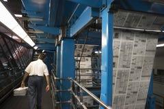 人运载的报纸堆在工厂 免版税库存照片