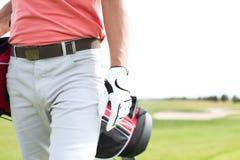 人运载的高尔夫俱乐部袋子的中央部位,当走在路线时 库存图片