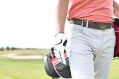 人运载的高尔夫俱乐部袋子的中央部位,当走在路线时 免版税图库摄影