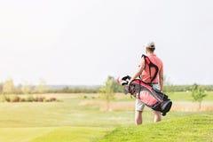 人运载的高尔夫俱乐部袋子背面图,当走在路线时 免版税库存照片