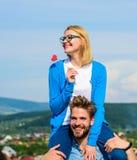 人运载肩膀的女朋友,天空背景 浪漫日期概念 妇女拿着在爱的棍子标志的心脏 免版税库存图片