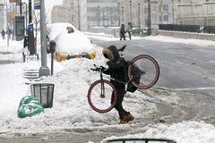人运载自行车,当穿过在雪风暴时的街道 免版税库存照片