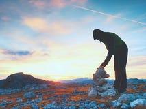 人远足者修造小卵石金字塔 在阿尔卑斯山山顶的石头 破晓天际 图库摄影