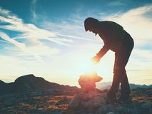 人远足者修造小卵石金字塔 在阿尔卑斯山山顶的石头 破晓天际 免版税图库摄影