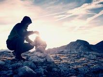 人远足者修造小卵石金字塔 在阿尔卑斯山山顶的石头 破晓天际 库存照片