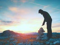 人远足者修造小卵石金字塔 在阿尔卑斯山山顶的石头 破晓天际 免版税库存照片