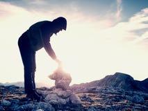 人远足者修造小卵石金字塔 在阿尔卑斯山山顶的石头 破晓天际 库存图片